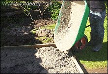 Concrete slab floor being poured from a wheelbarrow
